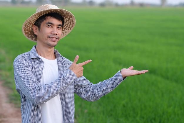 L'uomo asiatico del coltivatore in piedi e alza il punto della mano a lato alla fattoria del riso verde