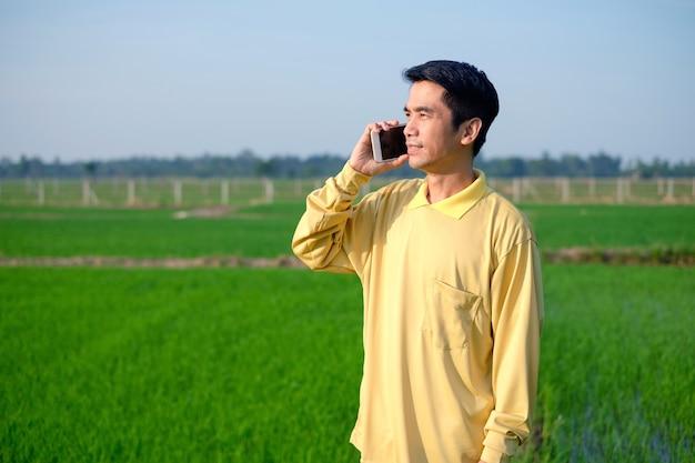 L'agricoltore asiatico indossa una camicia gialla in piedi e chiama con lo smartphone alla fattoria di riso verde.