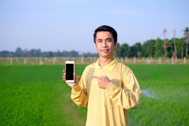 L'agricoltore asiatico indossa una camicia gialla in piedi e tiene in mano uno smartphone alla fattoria di riso verde.