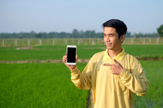 L'agricoltore asiatico indossa una camicia gialla tiene lo smartphone e lo guarda in una fattoria di riso verde