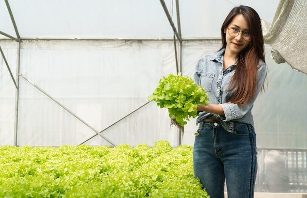 Donna asiatica dell'agricoltore che tiene verdura cruda