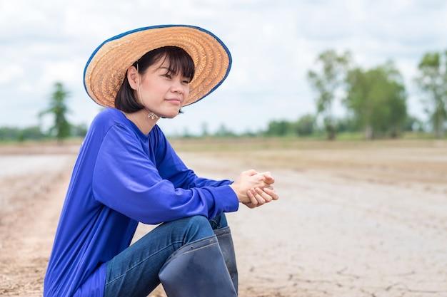 Donna asiatica dell'agricoltore triste e seduta alla fattoria del riso.