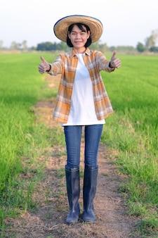 Sorriso e pollici asiatici della donna del coltivatore in su all'azienda agricola del riso verde.