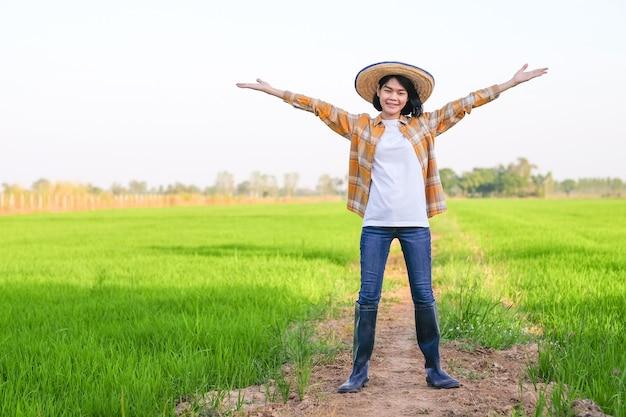 La donna asiatica del coltivatore in piedi e alza la mano alla fattoria del riso