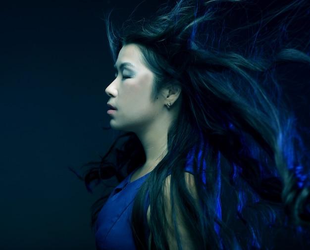 Donna asiatica alla moda con il vento tra i capelli