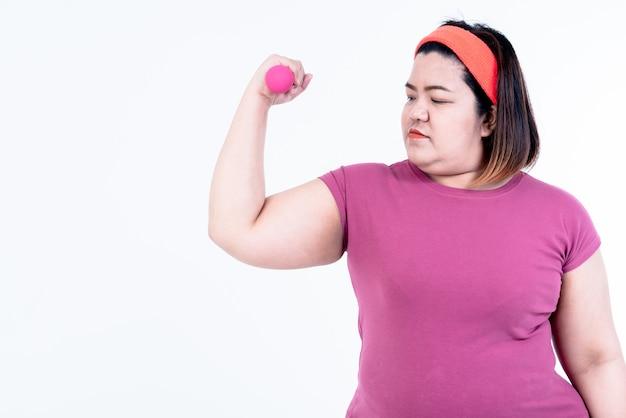 Donna grassa asiatica che si esercita, sollevamento pesi con manubri, per perdere peso