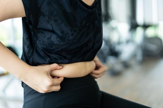 Donna grassa asiatica che afferra sulla sua pancia di stomaco