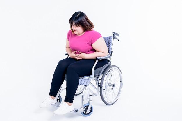 La donna grassa asiatica che si siede su una sedia a rotelle ha dolore allo stomaco proviene da gastrite