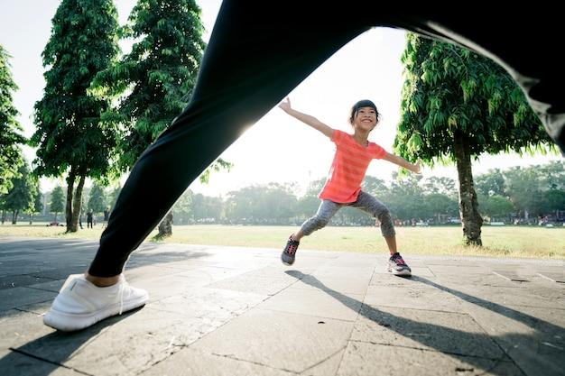 Padre e figlia asiatici fanno esercizi per prendere e giocare insieme