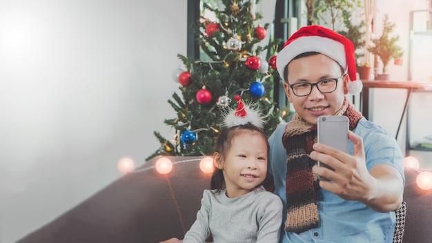 Padre e figlia asiatici che usando insieme selfie dello smartphone