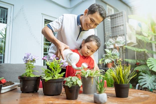 Padre e figlia asiatici che usando annaffiatoio per innaffiare le piante in vaso