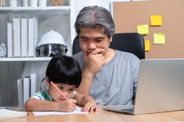 Il padre asiatico lavora a casa con una figlia e studia insieme l'apprendimento online da scuola.