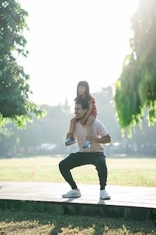 Il padre asiatico e la figlia piccola fanno esercizi nello stile di vita sano all'aperto della famiglia con bambino