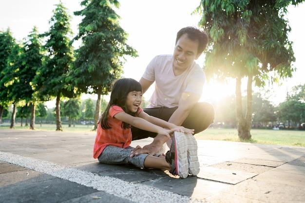 Il padre asiatico e la piccola figlia fanno esercizi all'aperto. stile di vita sano della famiglia con bambino