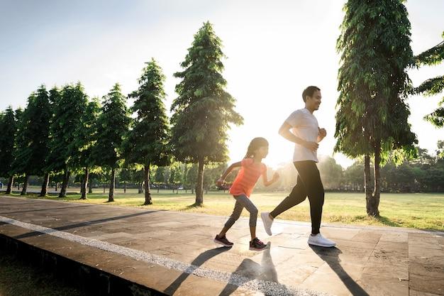 Il padre asiatico e la figlia piccola fanno esercizi in esecuzione all'aperto. stile di vita sano della famiglia con bambino