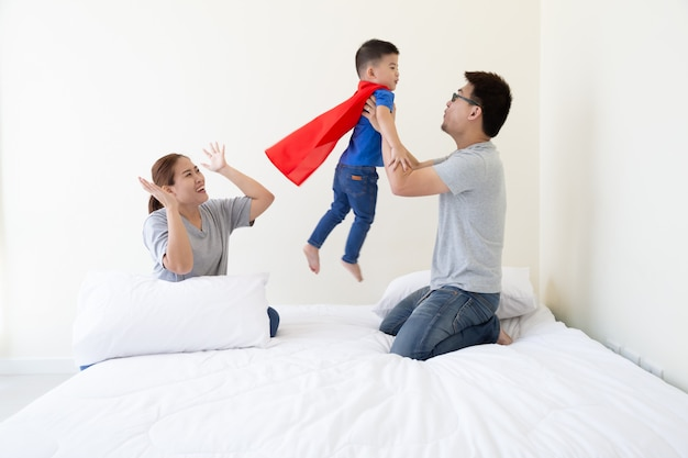 Padre, madre e figlio asiatici stanno giocando il supereroe sul letto in camera da letto. famiglia amichevole che si diverte