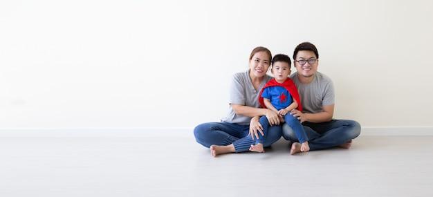 Padre, madre e figlio asiatici stanno giocando il supereroe sul pavimento nella stanza. buona giornata in famiglia Foto Premium