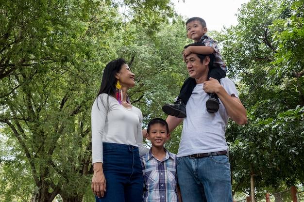 Padre, madre e figlio asiatici nel parco.
