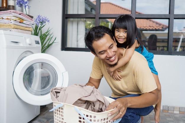 Padre asiatico che gioca a cavalluccio insieme alla figlia mentre fa il bucato usando la lavatrice