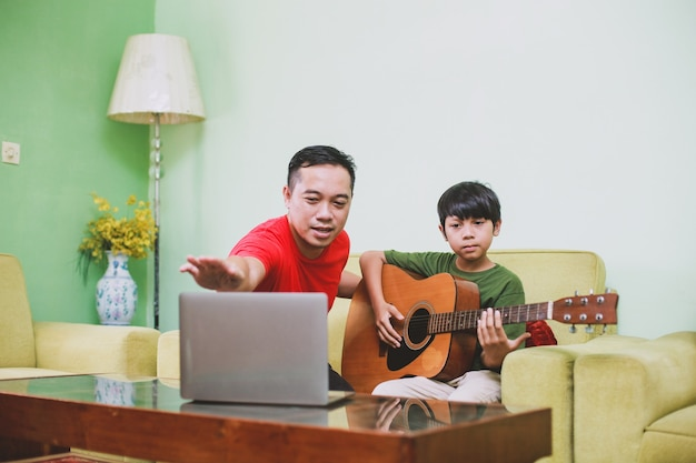 Il padre asiatico mostra come suonare la chitarra a suo figlio con il laptop