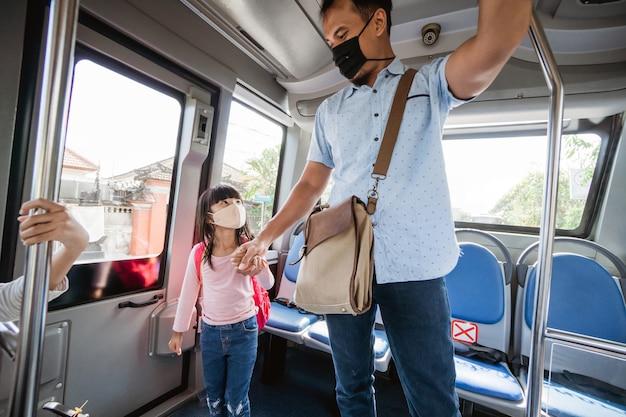 Padre asiatico che porta sua figlia a scuola in autobus con i mezzi pubblici indossando una maschera facciale