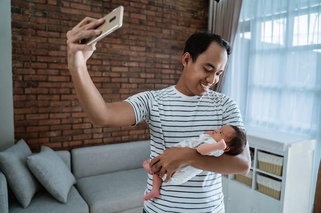 Padre asiatico con la figlia che prende selfie