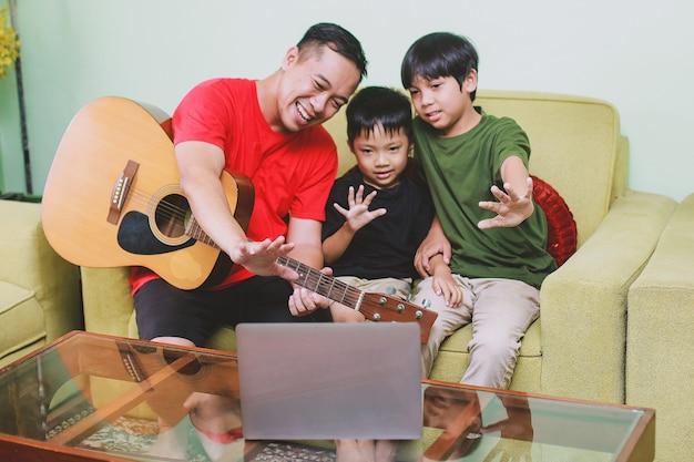 Padre asiatico con la chitarra che sorride insieme al computer portatile con suo figlio durante la videoconferenza