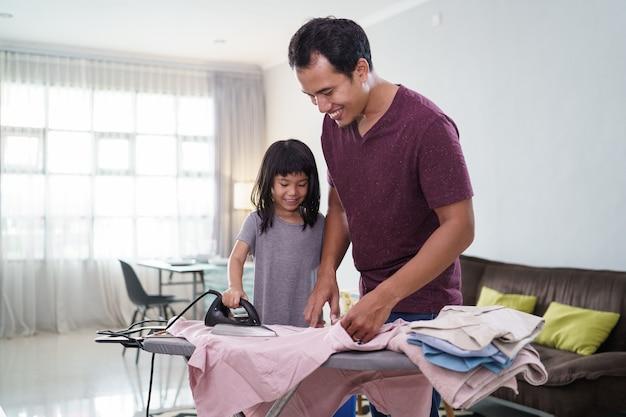 Padre asiatico con la piccola figlia stirare i vestiti a casa