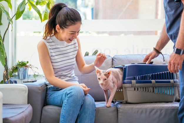 Femmina asiatica ad una clinica di adozione animale. riparo gatto con il nuovo proprietario dell'animale domestico.