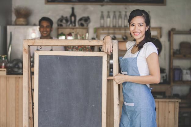Proprietario femminile asiatico del caffè con il bordo in bianco