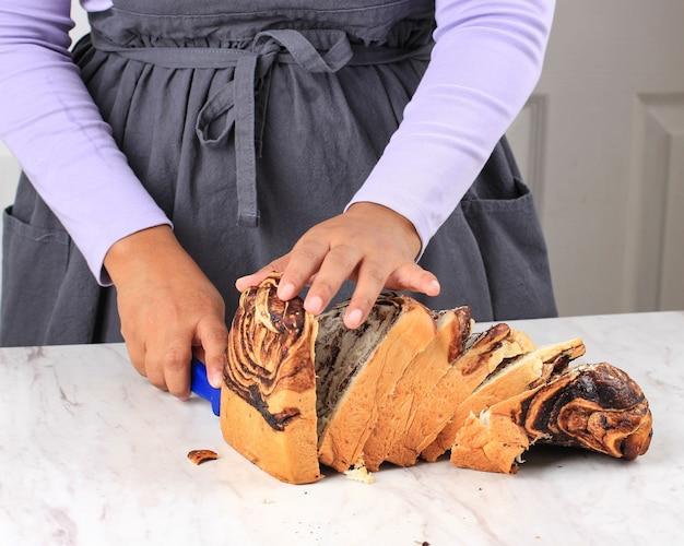 Asian femmina chef affettato a mano babka al cioccolato fatto in casa su sfondo bianco utilizzando il coltello. processo di cottura al forno in cucina. concept bakery