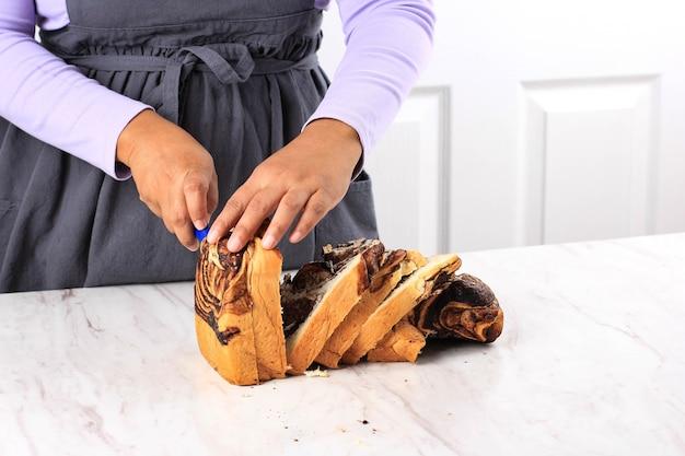 Asian femmina chef affettato a mano babka al cioccolato fatto in casa su sfondo bianco utilizzando il coltello. processo di cottura al forno in cucina