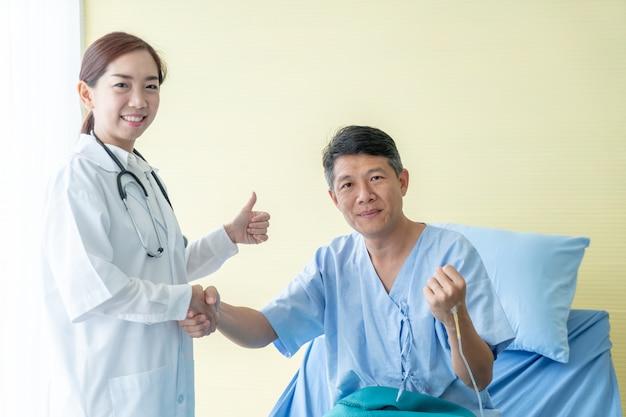 Medico femminile asiatico all'ospedale o alla clinica che dà una stretta di mano al suo paziente