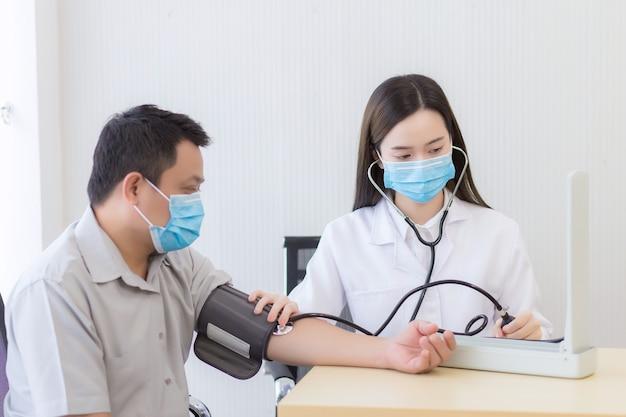 Una dottoressa asiatica misura la pressione sanguigna di un paziente uomo usando un misuratore di pressione sanguigna
