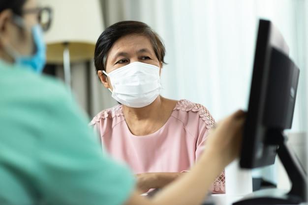 Medico o infermiere femminile asiatico in uniforme verde che parla dando consiglio al paziente anziano della donna in panno rosa e che guarda al monitor dello schermo di computer