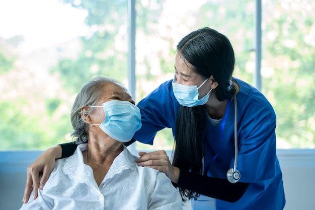 Medico femminile asiatico che supporta pazienti anziani,medico e donne anziane che indossano maschere facciali durante l'epidemia di coronavirus e influenza,protezione antivirus,covid-2019,assunzione di maschere.