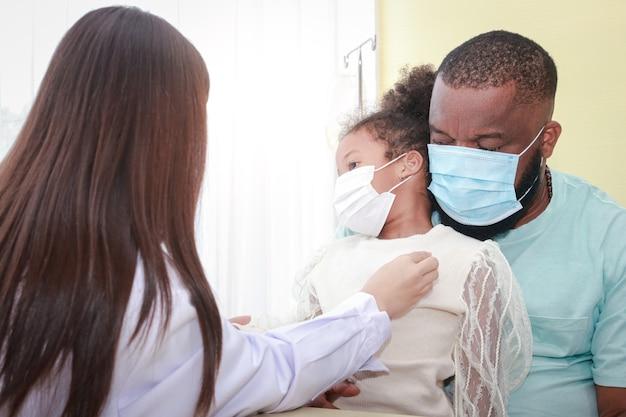 Una dottoressa asiatica usa uno stetoscopio controlla il battito cardiaco di una bambina afroamericana seduta con suo padre