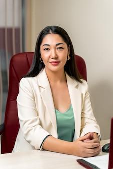 Medico femminile asiatico in camice bianco che si siede nella sedia rossa.