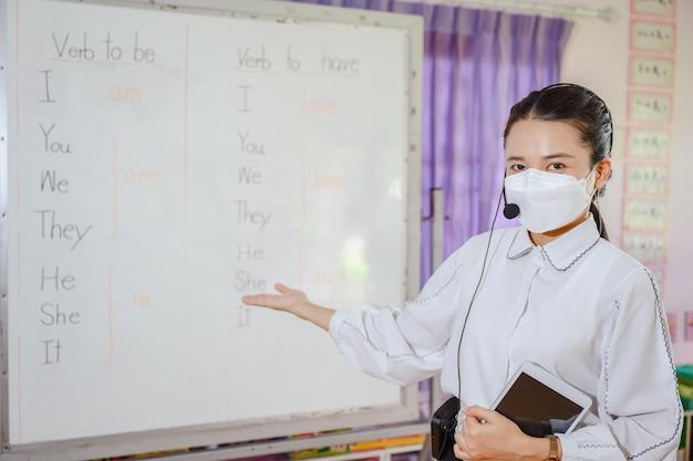 Insegnante di inglese femminile asiatica che indossa una maschera che insegna agli studenti a studiare online sullo schermo di un computer utilizzando un sistema di videoconferenza online per l'istruzione