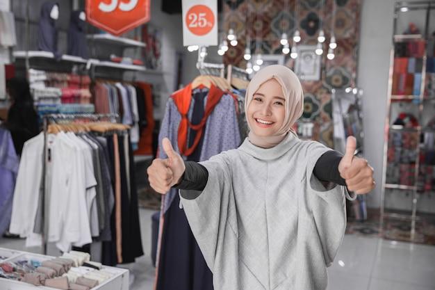 Proprietario di negozio di moda femminile asiatico che mostra pollice su