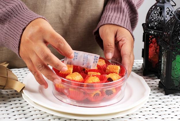 La mano femminile asiatica mette la confezione di gel di silice nel barattolo del contenitore dei biscotti nastar per assorbire l'umidità. prepara i biscotti sempre croccanti e deliziosi al negozio