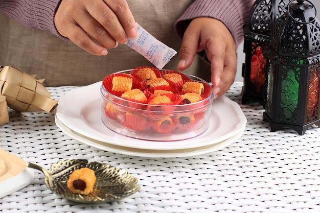 La mano femminile asiatica mette la confezione di gel di silice nel barattolo del contenitore dei biscotti nastar per assorbire l'umidità