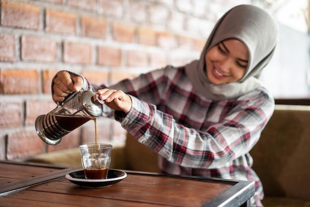 Femmina asiatica versare il caffè in una tazza in un caffè