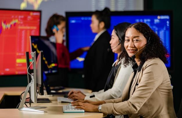 Il manager di borsa professionale femminile asiatico si siede sulla scrivania sorridendo davanti al monitor grafico guarda la telecamera mentre il team femminile dell'operatore del servizio clienti lavora in primo piano sfocato.