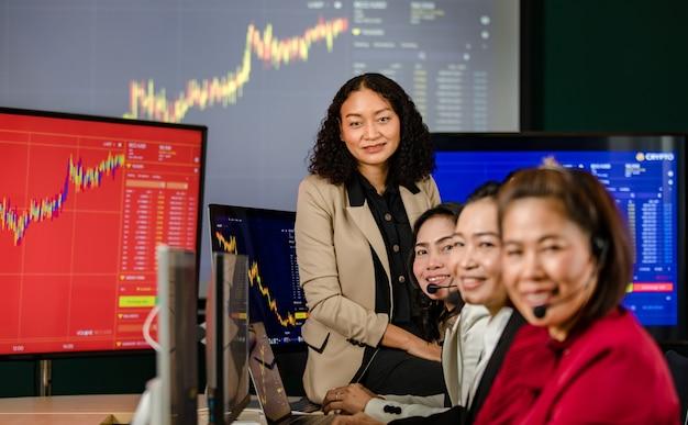 Il manager di borsa professionale femminile asiatico si siede sulla scrivania sorridendo davanti al monitor grafico guarda la telecamera mentre il team dell'operatore del servizio clienti indossa le cuffie del microfono che lavorano in primo piano sfocato.