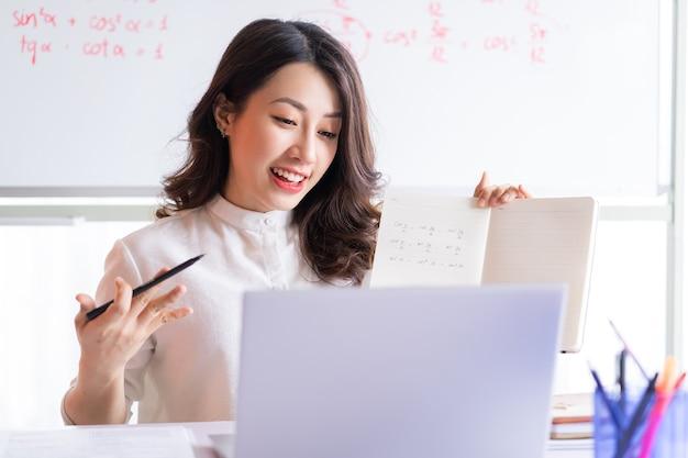Insegnante femminile asiatica che insegna in linea a casa