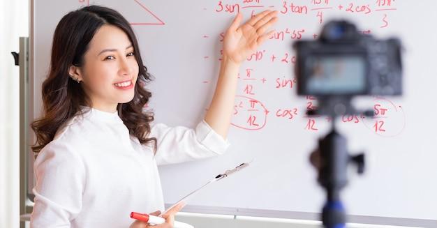 Le insegnanti asiatiche stanno registrando lezioni per il lavoro di insegnamento online