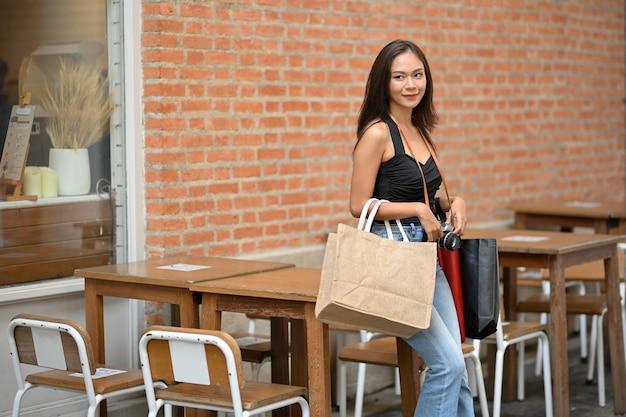 Turista asiatica che viaggia in città estiva appoggiata al tavolo con le borse della spesa in mano