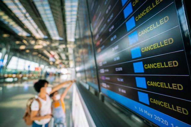Viaggiatore femminile asiatico che osserva sulla scheda di informazioni di voli in aeroporto