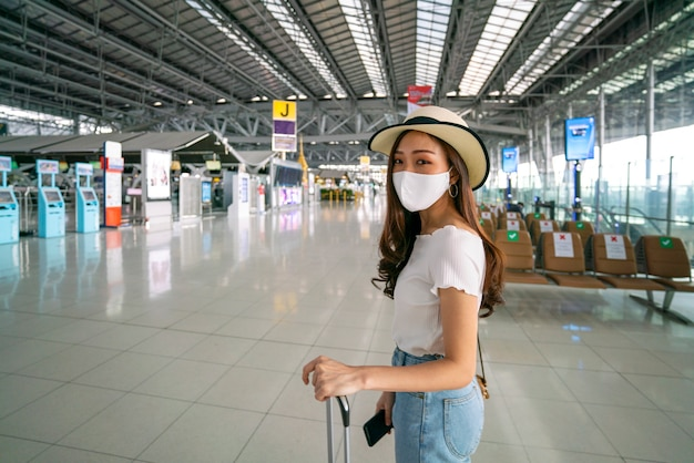 Viaggiatore femminile asiatico che indossa la maschera per il viso mantenere la distanza con altri viaggiatori in aeroporto